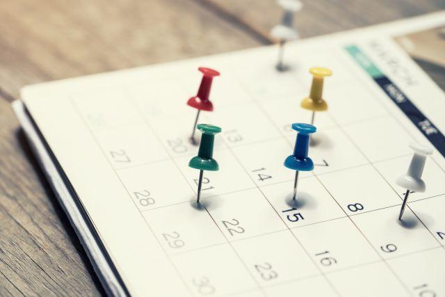 Bunte Pins im Kalender auf Holztisch