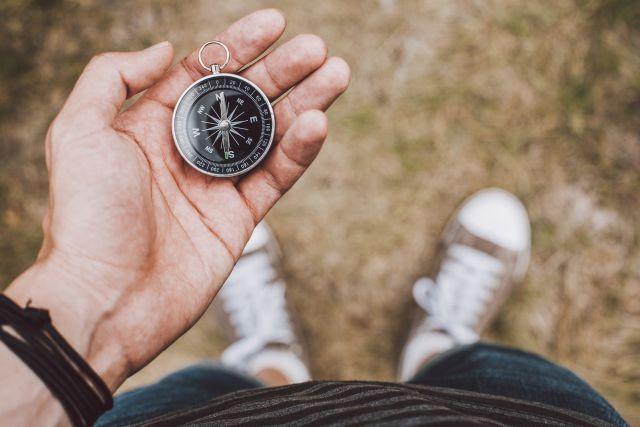 Wanderer hält Kompass in der Hand und sucht nach dem richtigen Weg