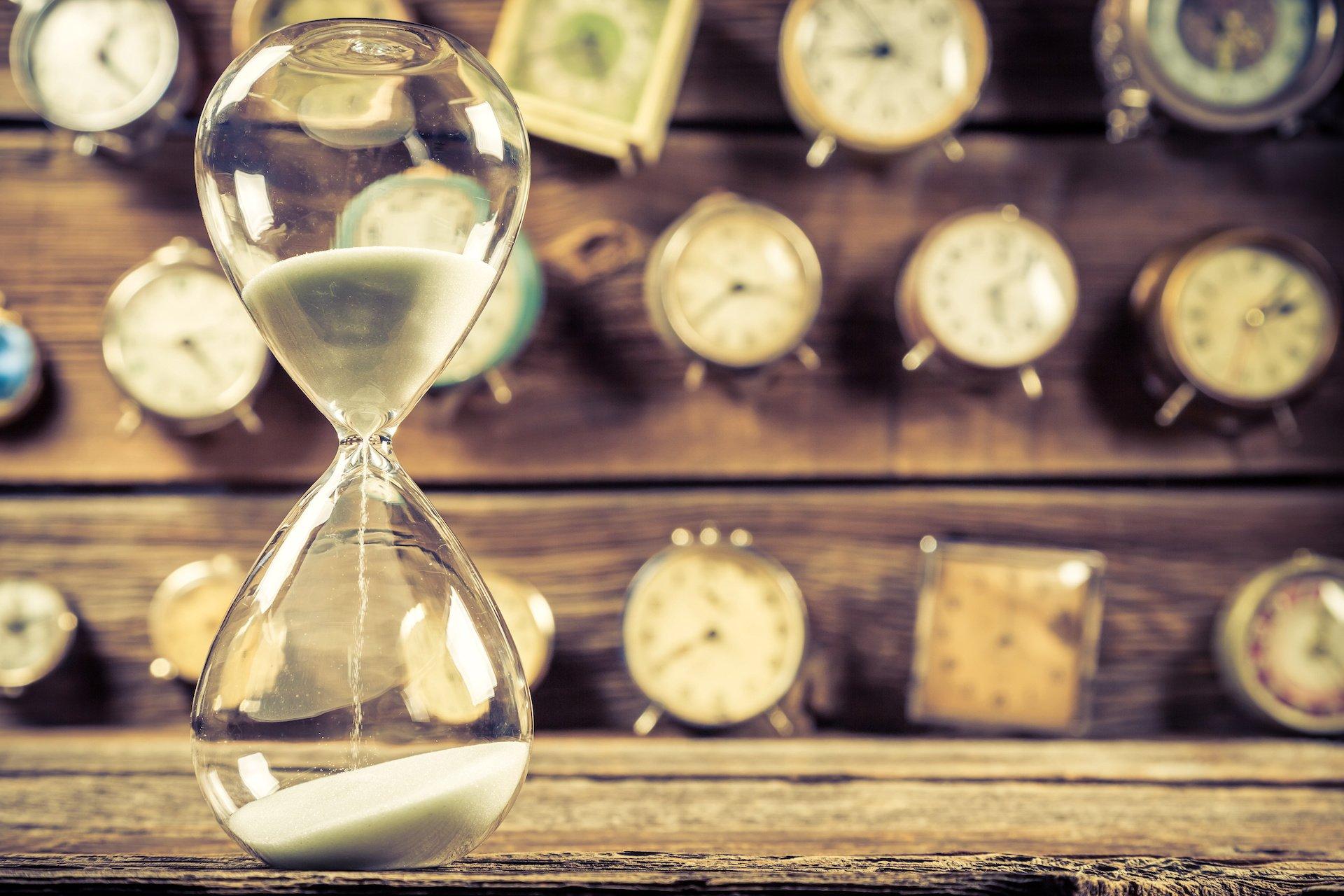 Vintage Sanduhr vor Uhren auf Holzwand