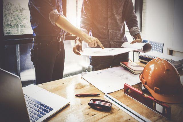 Zwei Projektleiter am Schreibtisch besprechen Bauprojekt