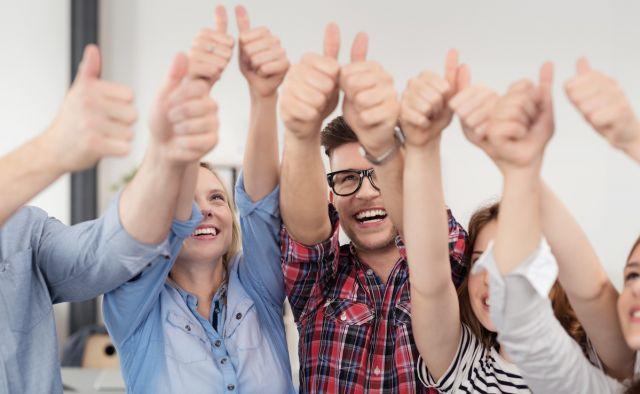 Erfolgreiches Team im Büro zeigt Daumen hoch