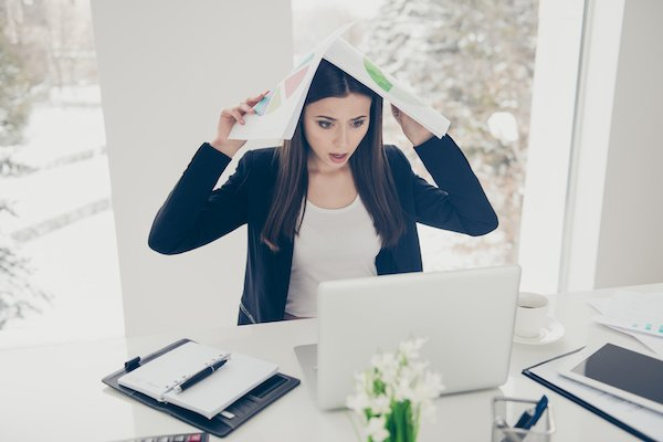 Überlastete Projektleiterin hält Dokumente über Ihren Kopf und schaut erschrocken auf einen Laptop