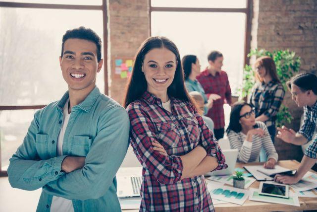 Zwei junge, smarte Projektleiter stehen lässig im Büro und freuen sich über Arbeitserfolge
