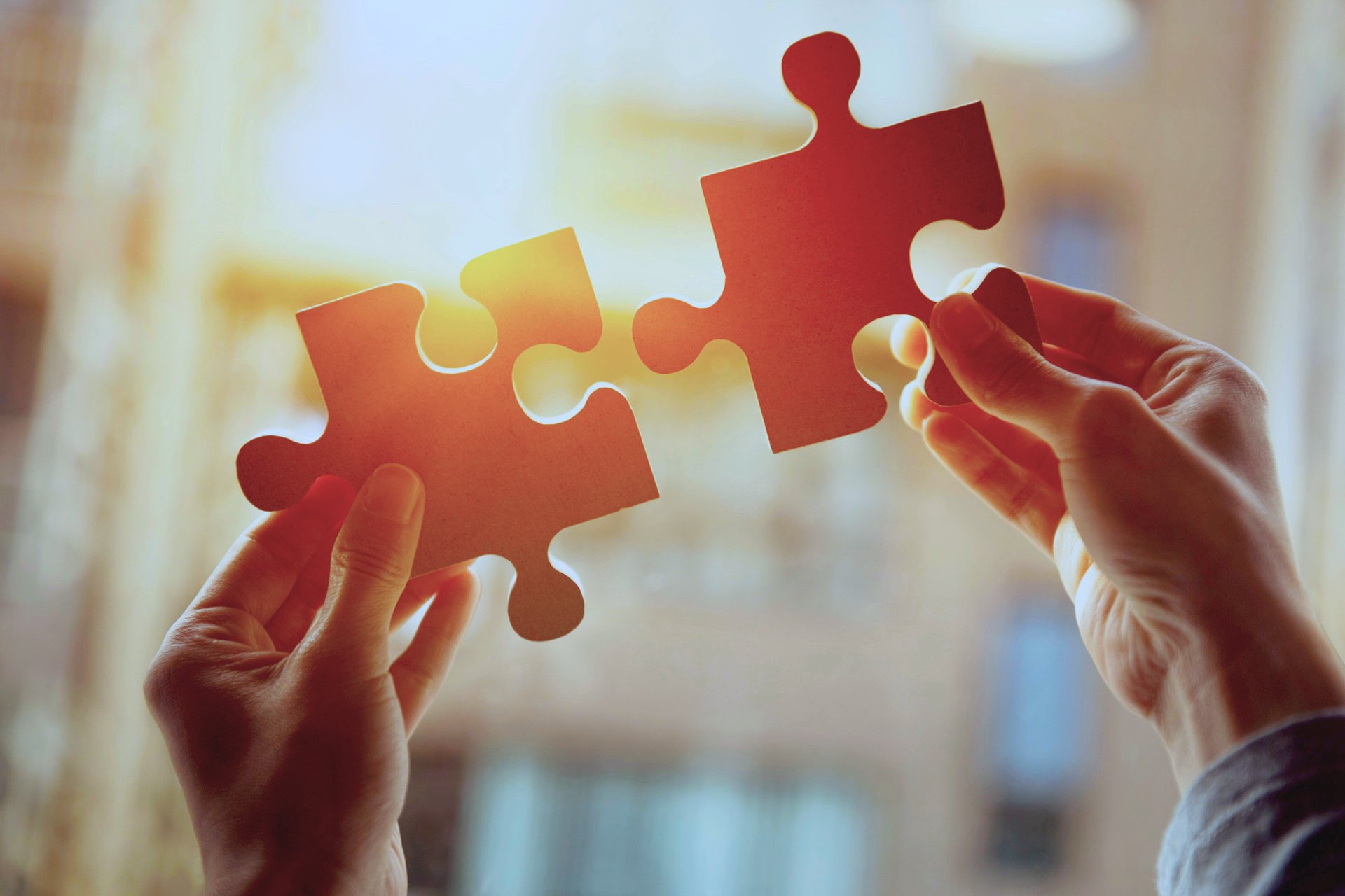 Hände einer Businessfrau mit zwei Puzzlestücken
