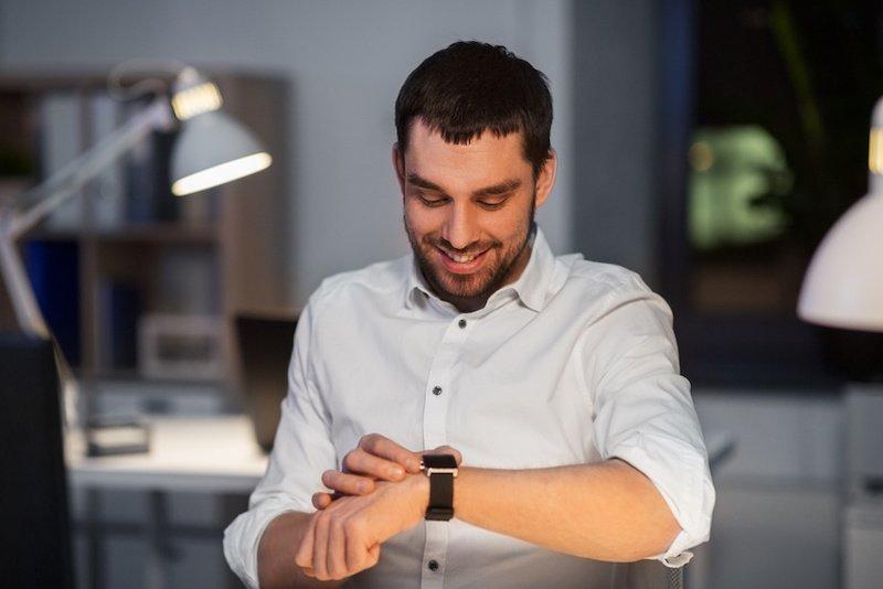 Projektmitarbeiter schaut auf seine Uhr und lächelt