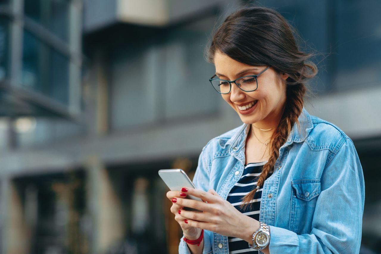 Junge Frau liest unterwegs eine Nachricht auf ihrem Smartphone