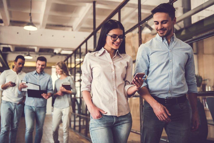 Erfolgreiches Team benutzt mobile Endgeräte, unterhält sich, lächelt und geht entlang eines Korridors