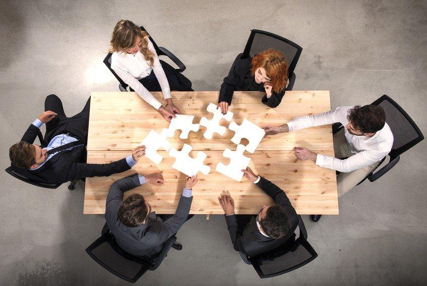 Ein Team setzt am Tisch einzelne Puzzlestücke zusammen