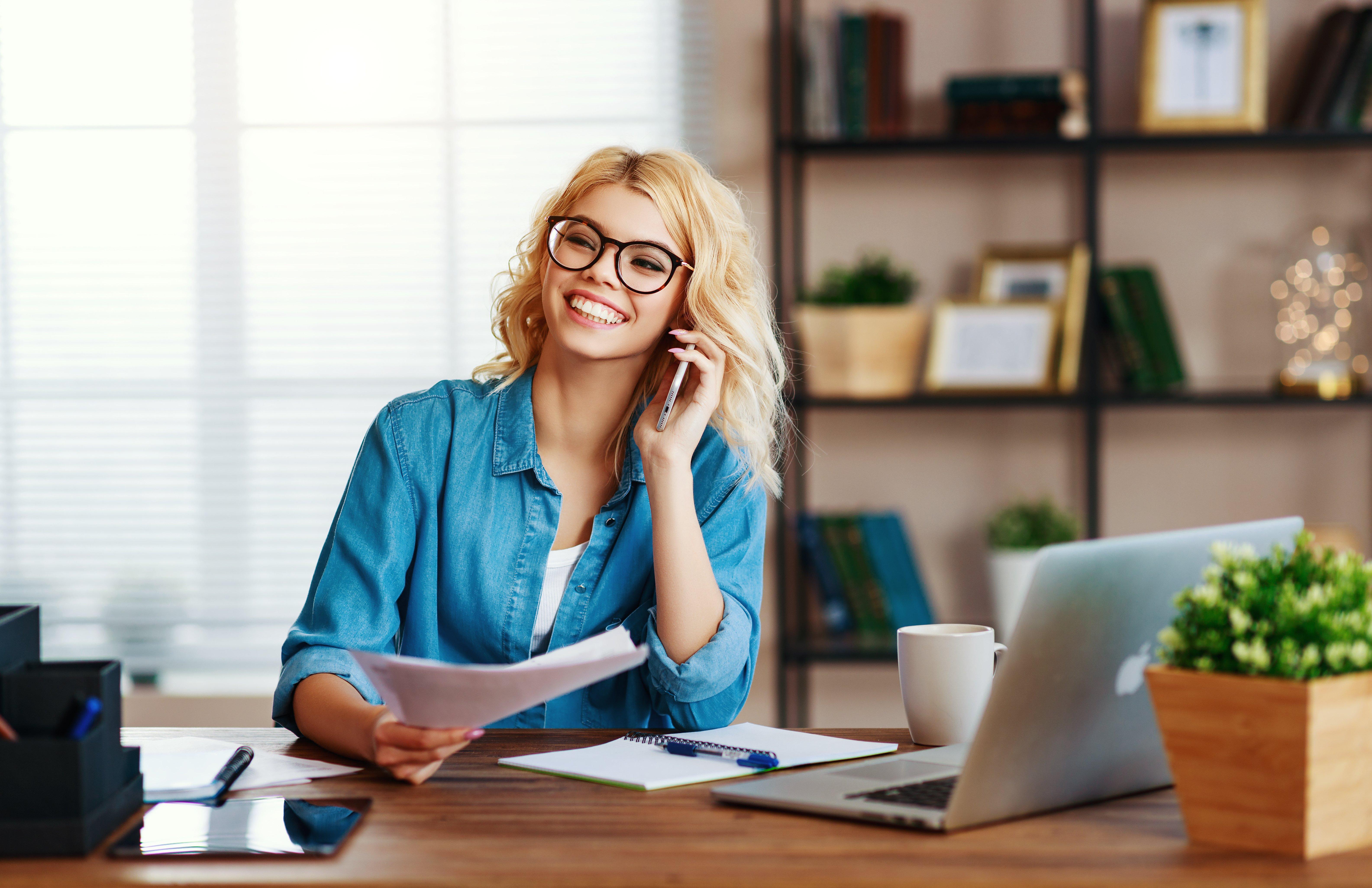 Eine junge Frau arbeitet im Home Office und ist fröhlich