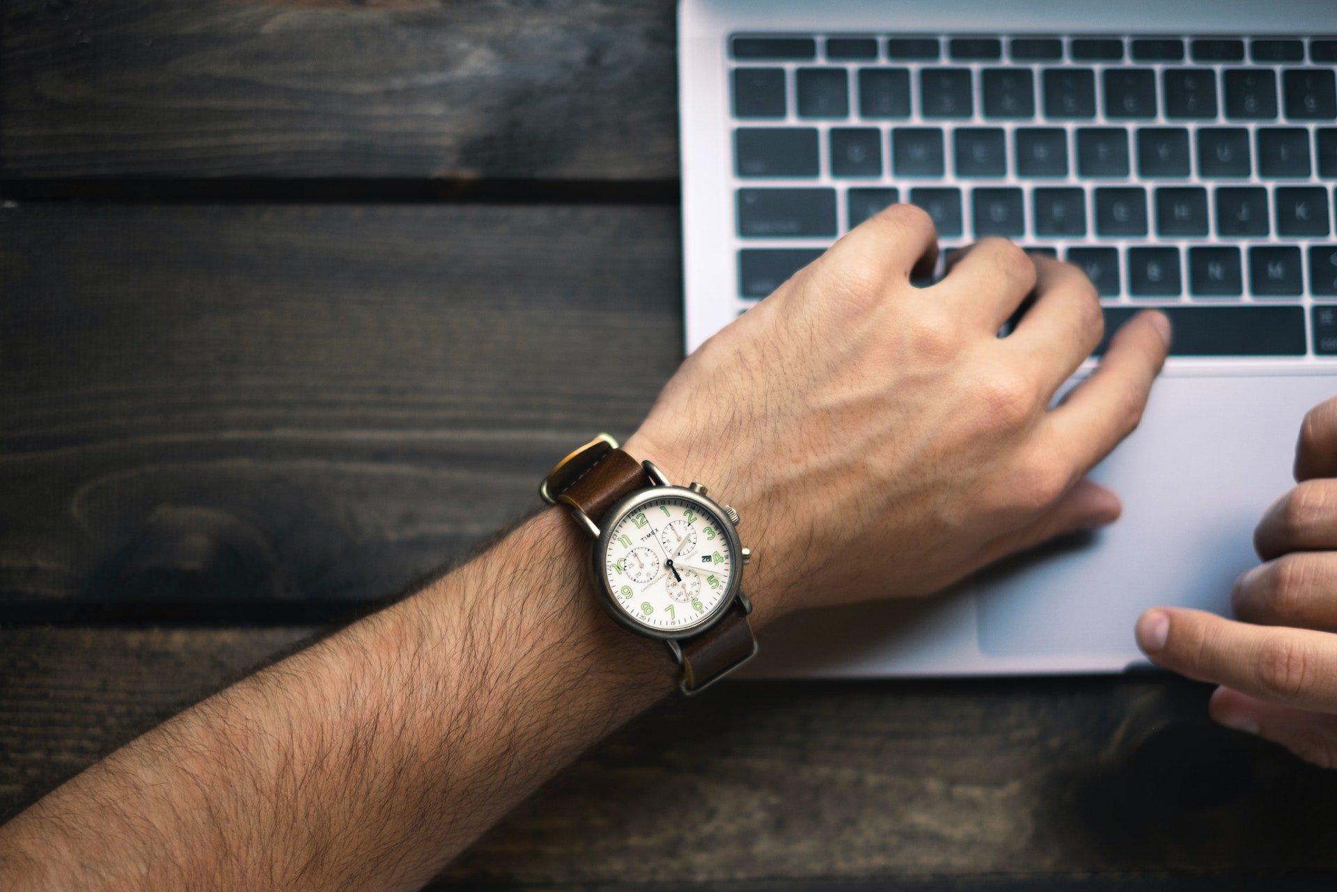 Ein junger Mann schaut am Laptop auf die Uhr