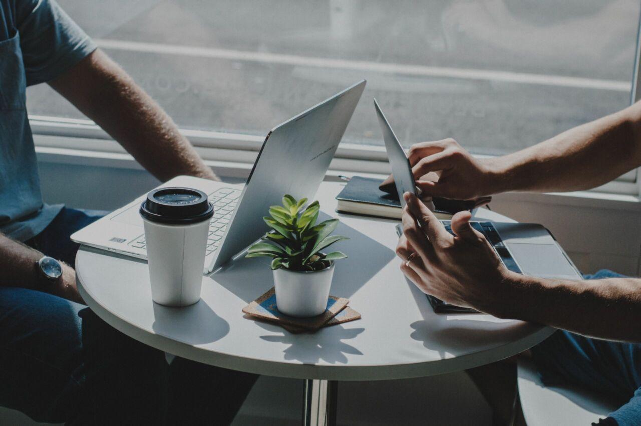 Zwei Menschen im Interview mit Ihren Laptops in einem Cafe