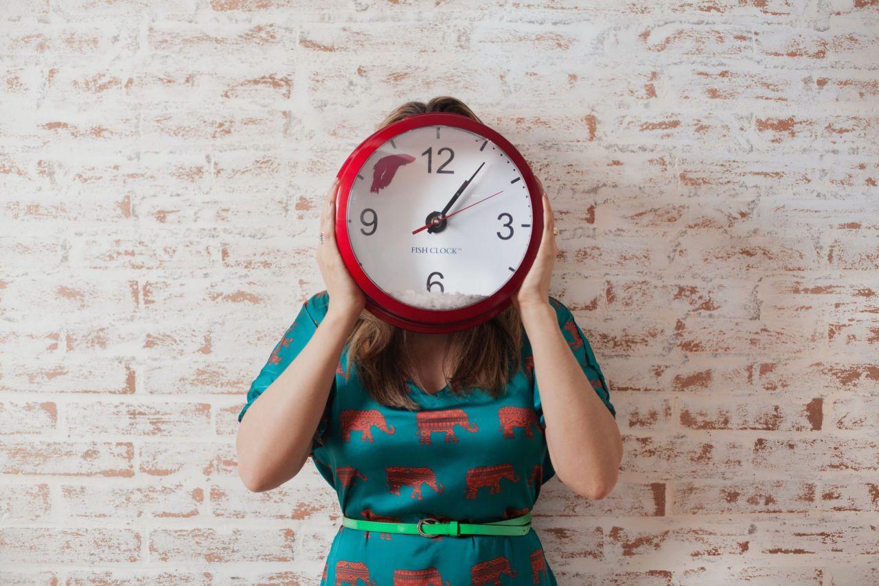 Eine Frau hält eine Uhr vor das Gesicht