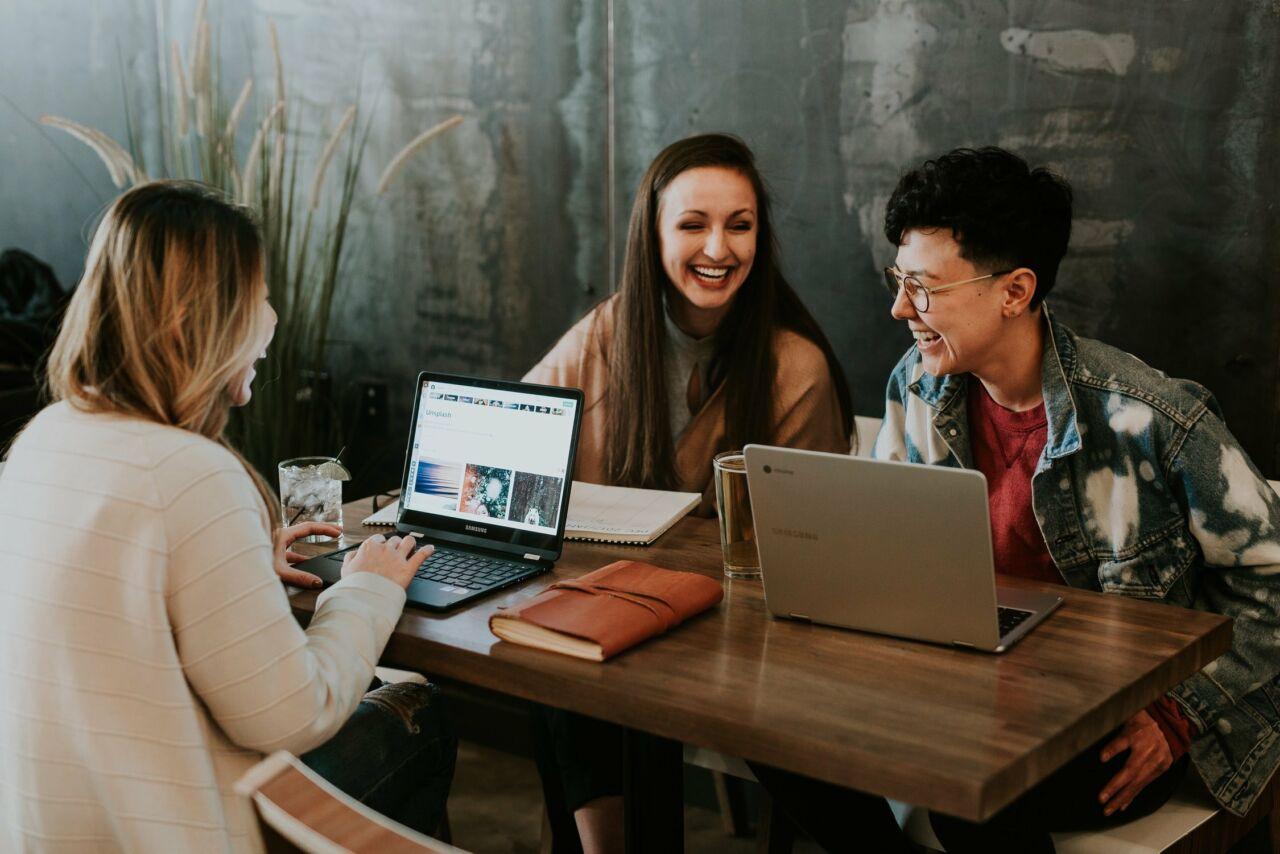 Drei Frauen sitzen vor ihren Laptops und lachen gemeinsam