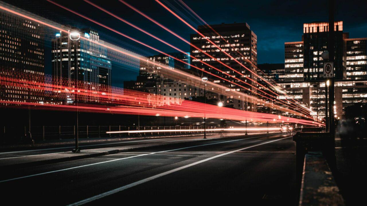 Eine Straße im dunkeln mit einer Stadt im Hintergrund