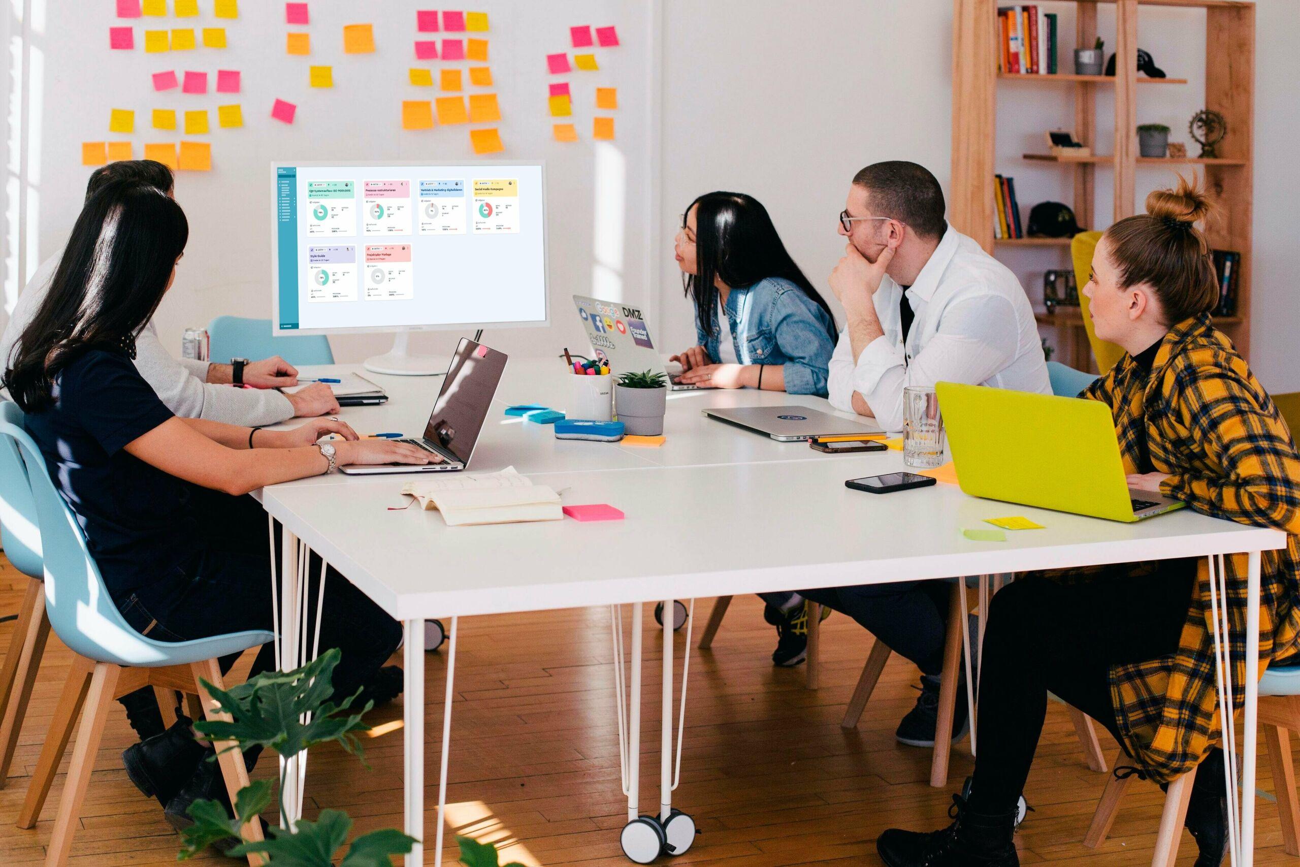 Projektteam sitzt am Schreibtisch und schaut auf einen Beamer